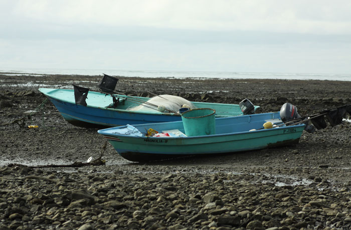 two fishing boats on rocks